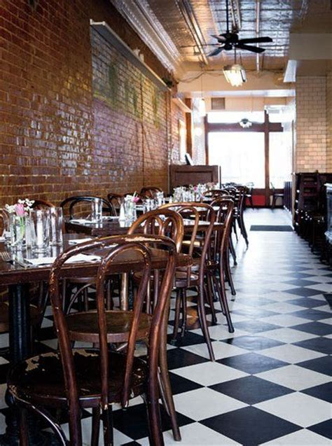 Black-and-white tile floors, brick walls, a tin ceiling